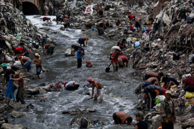 Guatemalans mining for metals or recyclables they can sell from Guatemala City's garbage dump. Photo: Rodrigo Abd, Associated Press photographer, The Boston Globe