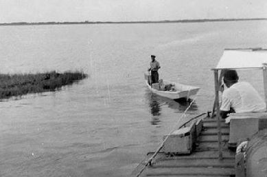 Henry Pigott poles out to greet the Aleta off Porstmouth Island in this circa 1953 photo. That's Capt. Elmo Fulcher at the helm. Photo:Friends of Portsmouth Island