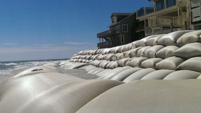 The sand structures in in front of the sand-bag wall at North Topsail violate the state permit and must be removed, state official say. Photo: Frank Tursi