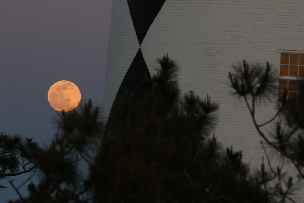 While observing the sun set over Lookout Bight, I turned to see that the full moon had lifted above the horizon and was rising parallel to the base of the lighthouse.