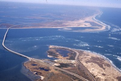 An unusual solution to the inlet's woes is contained in a bill passed by the N.C. General Assembly last year. It instructs state officials to begin negotiations with the federal government to acquire its land at Cape Hatteras National Seashore, top of photo, and at Pea Island National Wildlife Refuge, at the bottom. Photo: Outer Banks Voice