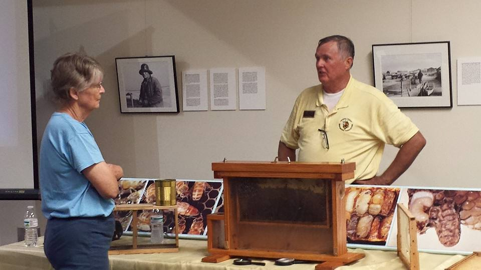 Beekeeper Randall Russell Lewis, right, shares his knowledge of current honey making