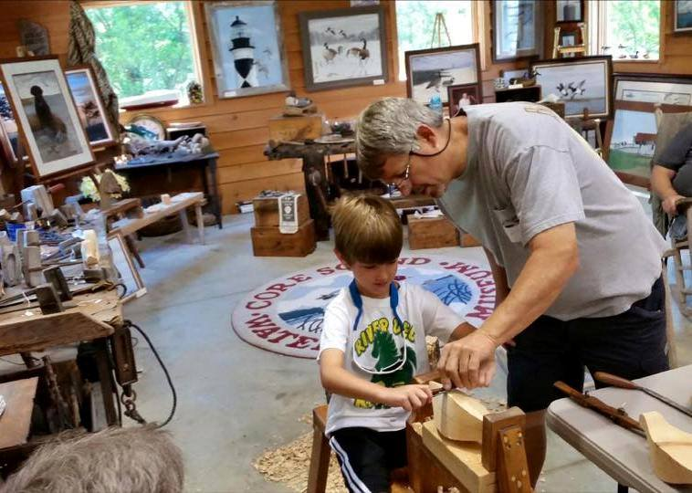 Waterfowl carvers demonstrate techniques of carving functional decoys as part of the summer program.