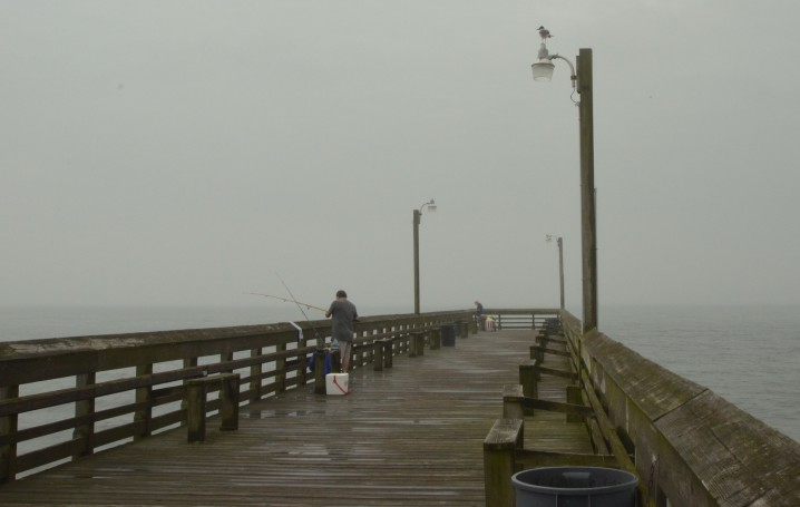 """Pat Moss of High Point came to fish on the Holden Beach Pier on a rainy morning.  """"I don't have a problem with it [offshore drilling] as long as it's regulated,"""" he said. """"Then again, the oil companies have the regulators in their pockets."""" Photo: Tess Malijenovsky"""