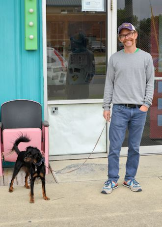 """Wilmington native Dan Brawley with his dog Izzy in front of Jengo's Playhouse. He says, """"I think it's absolutely outrageous, ridiculous—when you look at the fragile ecosystems that are disrupted by that type of activity it's a no-brainer. We're living in literally, right now, the greatest mass extinction that's ever taken place on this planet, and it's our fault."""" Photo: Tess Malijenovsky"""