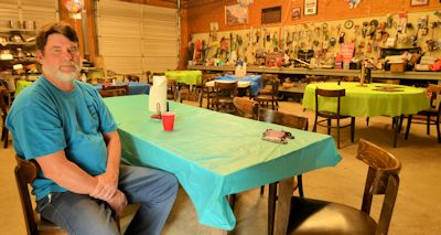"""Jerry Edens, a commercial waterman native to Topsail, sits inside his garage where every Monday, Thursday and Friday he invites his family and friends to eat, drink and socialize. He works close to the shore and says, """"As long as it's far enough offshore, it ain't going to bother us.""""  Photo: Tess Malijenovsky"""