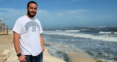"""John Pletl stands on top of the giant sandbag wall protecting North Topsail. He lives across the street where he grew up. """"I'm for drilling,"""" he says, """"just not offshore.""""  Photo: Tess Malijenovsky"""