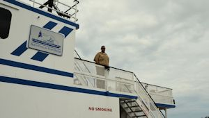 Chris Pittman keeps a lookout, working on the Southport ferry. He says offshore drilling would boost the local economy and bring more maritime jobs.  Photo by Tess Malenjovsky