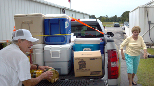Amy Wetherington, left, and Sharon Johnson, members of Carteret-Craven Electric Cooperative, pile a truck high with coolers at A Second Helping – Emerald Isle. Photo: George Gardner