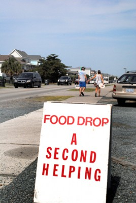 It's leaving time at Holden Beach, and a line of departing cars – plus a hand-holding couple – form a backdrop for Second Helping's food collection. Photo: Hannah Miller