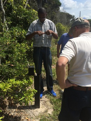 Alex Manda demonstrates for volunteers how to take a groundwater level reading using a handheld meter at a well location in Pine Knoll Shores. Photo: Mark Hibbs