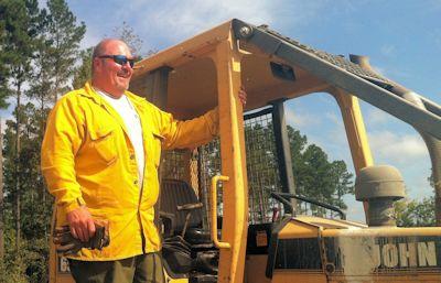 Matt Turner waits atop a bulldozer and look for any stray sparks. Photo: Allison Ballard