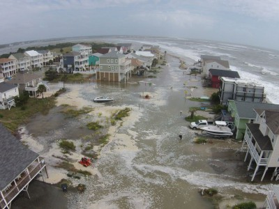 High tide Sunday brought the ocean over the dunes in Ocean Isle. Photo: Christopher Surigao