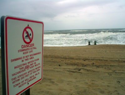 Permanent signs warning swimmers against possible pollution were posted about 10 years ago at all  ocean outfalls on the Outer Banks. Photo: Coastal Studies Institute