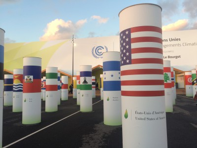 Pillars at the conference entrance, each decorated with a different national flag, illustrate the sense of unity in the global mission to stem global warming. Photo: Cate Kozak