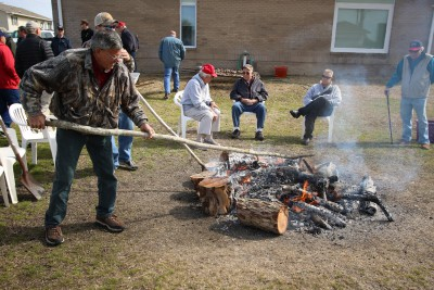 Members of the Salter Path Men's Club stoke the fire in preparation for steaming oysters. Photo: Sam Bland