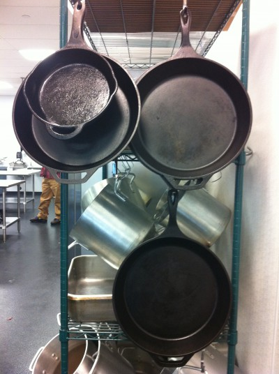 Still relevant: Cast-iron skillets hang among the more common stainless steel pans students use at The Chef's Academy, a culinary school in Morrisville, near Raleigh. Photo: Liz Biro