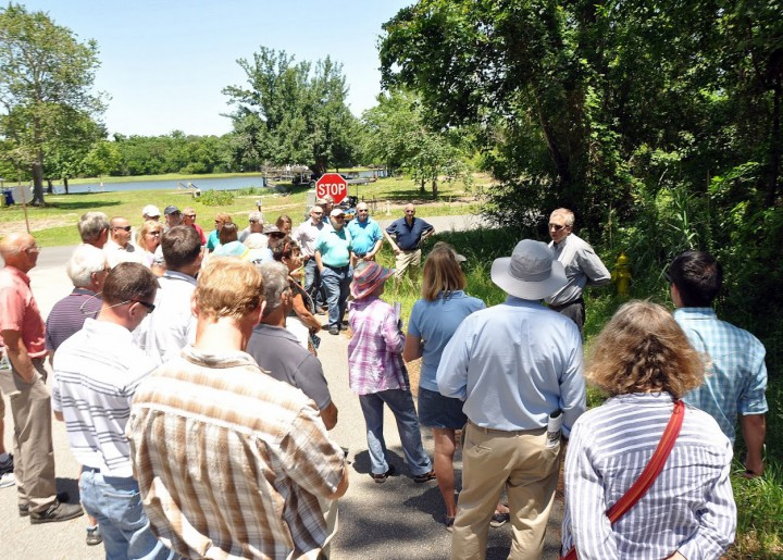 Civil engineer Larry Sneeder describes how swales function to the group that recently toured Oak Island. Photo: Todd Miller