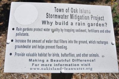Signs describe the stormwater mitigation projects at sites, including this rain garden, on Oak Island. Photo: Todd Miller