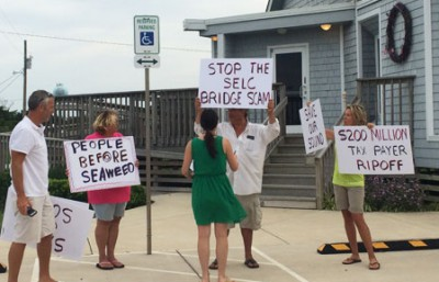 A small group of north Rodanthe property owners gather outside the Rodanthe-Waves-Salvo Community Building to protest NCDOT's chosen alternative for bridging the S-curves and Mirlo beach. Photo: Island Free Press