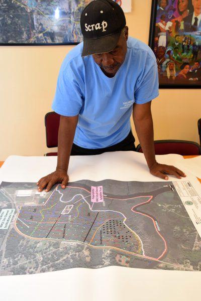 Mayor Eulis Willis looks over an aerial photo showing contaminated sites in Navassa. Photo: Mark Hibbs