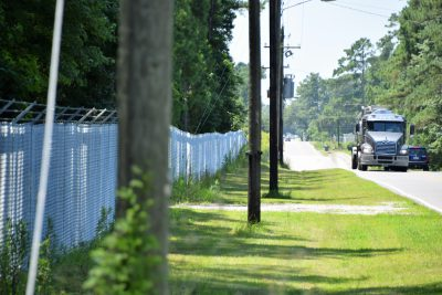 Traffic passes by the fenced-off Kerr-McGee Chemical Corp. site that's just off the highway leading into Navassa. Photo: Mark Hibbs