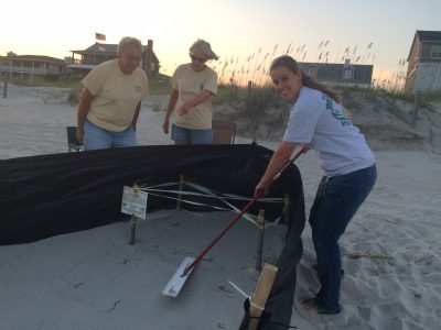 Michele Lamping, right, smooths sand to provide baby turtles a clear path to the ocean during a nest sitting with volunteers Mike and Barb Basher. Photo contributed