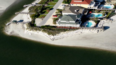The CRC waived the rules to the owners of this threatened house on Ocean Isle to build a bigger sandbag. Photo: N.C. Division of Coastal Management