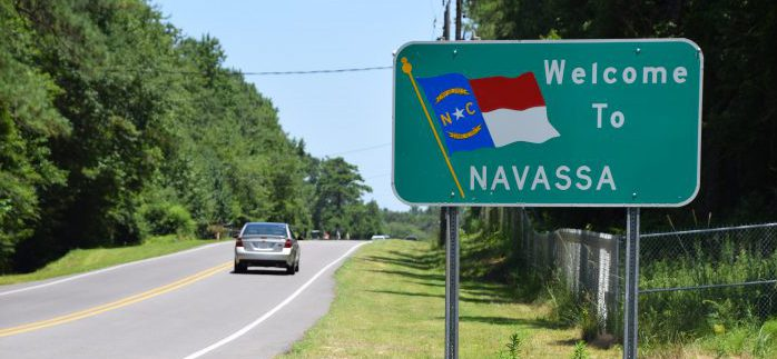 A welcome sign and the fenced-off Kerr-McGee Chemical Corp. site greet visitors at the Navassa city limits. Photo: Mark Hibbs