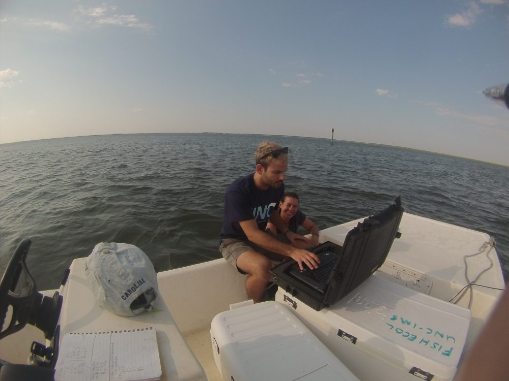 Danielle Keller and fellow doctoral student Ian Kroll check on data from hydrophones that tracktagged fish. Photo: Ashita Gona