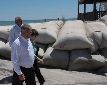 Reps. John Torbett, Pat Hurley and Phil Shepard walk past a sandbag wall during a recent legislative tour of North Topsail Beach to see the erosion problems. Photo: Kirk Ross