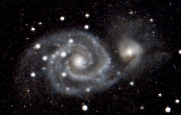 M51 is about 23 million light years away. The smaller galaxy on the right is NGC 5195. It's often called M51B. And yes, there is some sort of interaction going on between the two. Photo: Gerry Lebing