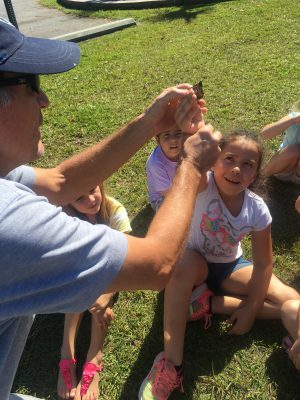 Sam Bland, left, shows students at Swansboro Elementary how to release a tagged monarch. Photo: Kat Lester