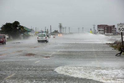 Vehicles pass as water rises on the U.S. 64 causeway near Whalebone Junction. Photo: Matt Lusk Photography