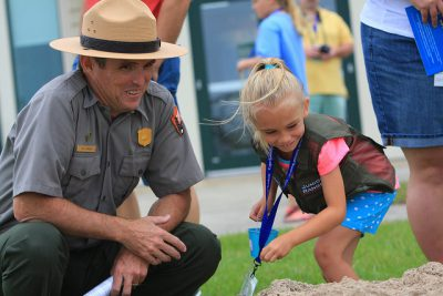 Pat Kenney celebrates the 50th anniversary of Cape Lookout National Seashore with a junior ranger. Photo: Britt Brown, National Park Service