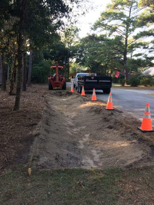 Public works employees at Pine Knoll Shores dig swales on the side of a road. Photo: Bree Tillett