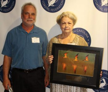 North Carolina Coastal Federation Director Todd Miller presents a 2016 Pelican Award on Aug. 6 to Jan Harris of Sunset Beach in recognition of her coastal advocacy. Photo: Sam Bland