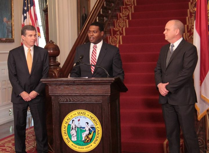 Michael Regan, Gov. Roy Cooper's pick to lead the Department of Environmental Quality, speaks Tuesday, flanked by Cooper, left, and newly named Transportation Secretary  Jim Trogdon. Photo: Kirk Ross