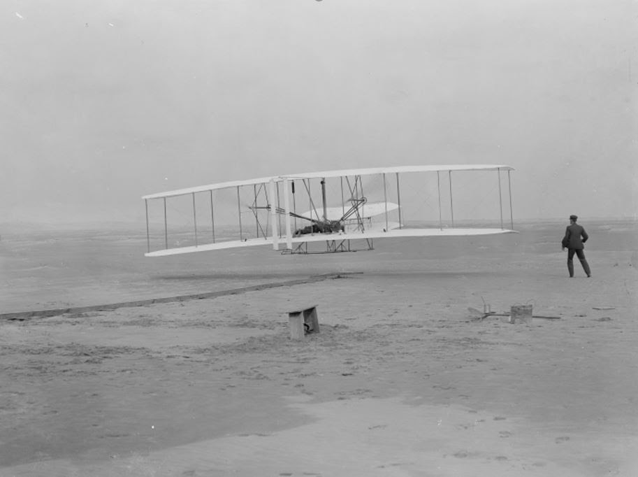 Orville Wright takes off in the first flight of the 1903 flyer as Wilbur Wright assists. Photo: National Park Service