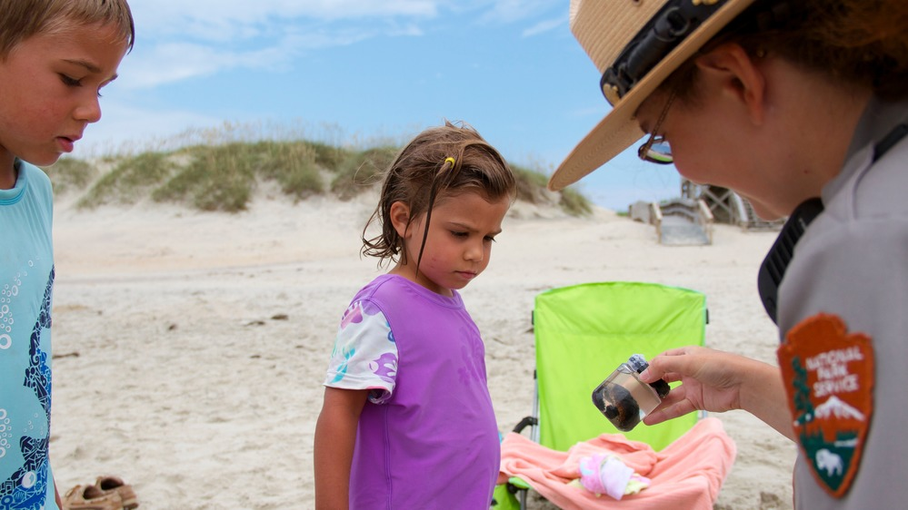 A ranger at Cape Hatteras National Seashore talks to young beachgoers about sea turtles. During National Outdoor Month in June, land managers urge visitors to protect natural resources. Photo: National Park Service