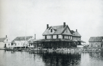 """The Doxsee clam factory, Ocracoke, N.C., early 1900s. Originally based in Islip, N.Y., the Doxsee family relocated its main operation to Ocracoke in 1897-98. According to Ocracoke historian Phillip Howard, """"most of the island's young, unmarried women, as well as several widows, worked at Doxsee's picking clams."""" Local watermen such as """"Big Ike"""" O'Neal supplied the factory with clams. Photo courtesy of Phillip's wonderful Village Craftsmen blog and the Doxsee family."""