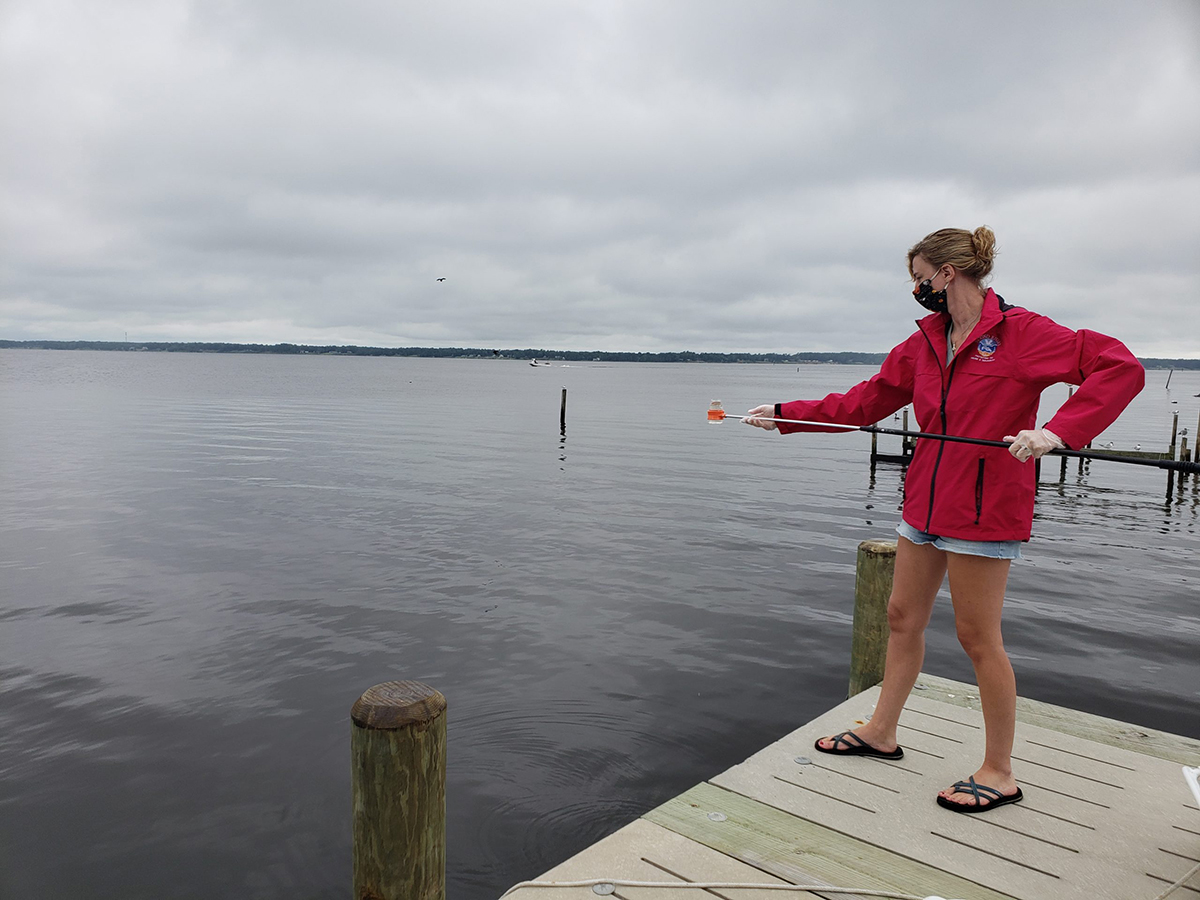 Lower Neuse Riverkeeper Katy Hunt collects water samples earlier this month to test for E. coli at Broad Creek off the Neuse River near a wastewater treatment plant. Photo: Sound Rivers
