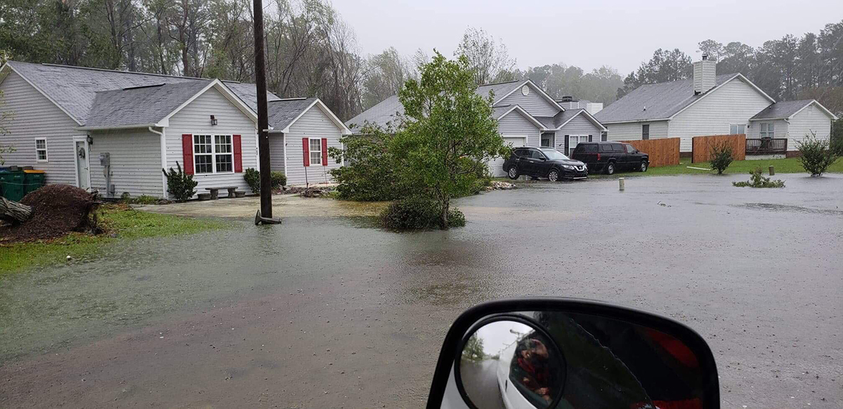Mark and Zena Underwood's house, gray with red shutters, is shown as water approaches during Hurricane Florence in 2018. They have since relocated and received state assistance toward a new home via a program that also took the property above off the market. Photo: Zena Underwood