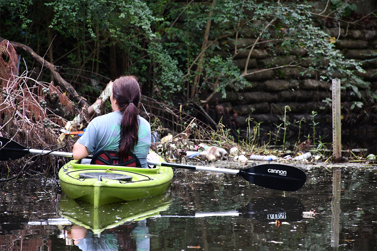 A paddler encounters plastic waste and other man-made debris in a tributary of Greenfield Lake in Wilmington. Photo courtesy of Cape Fear River Watch