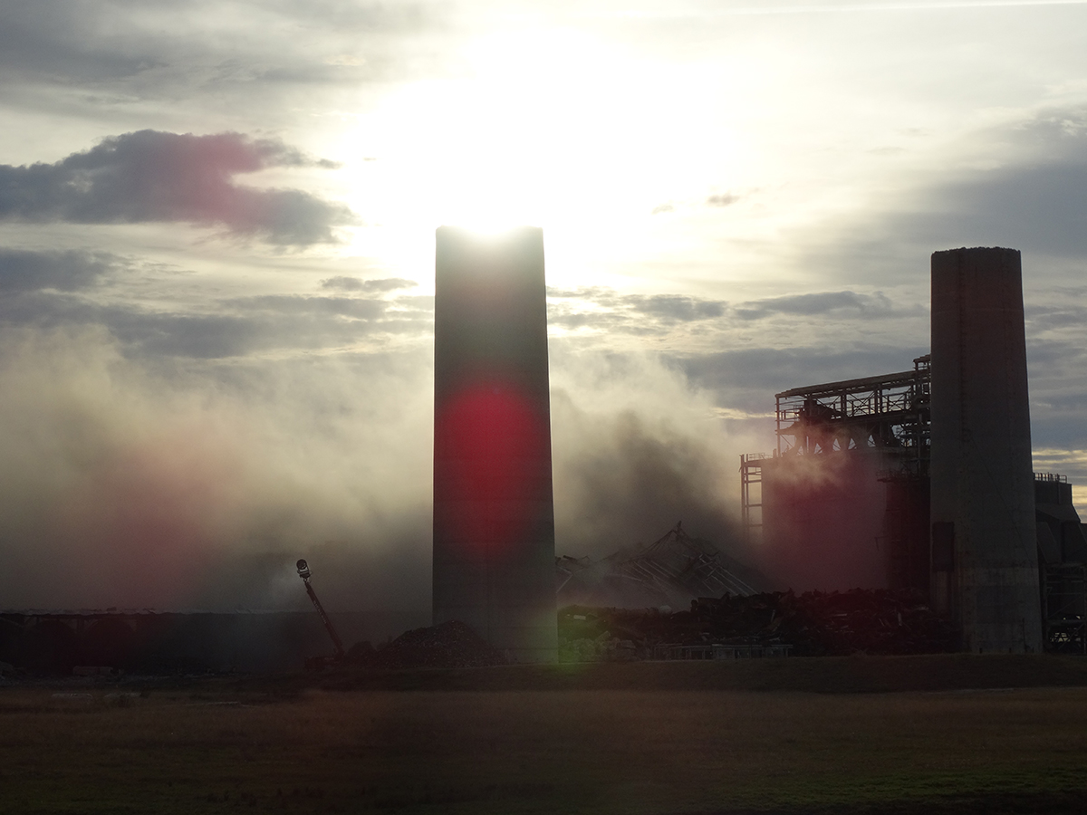 The remains of the two smokestacks at Duke Energy's former coal-fired Sutton Plant in Wilmington loom over the demolished boiler and coal silos in 2016. Photo: Duke Energy