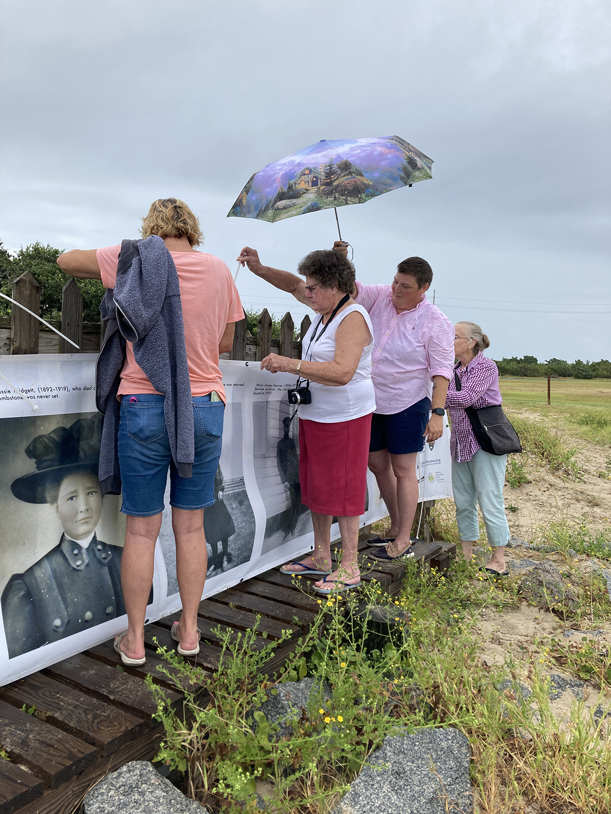 Jean Hooper, center, whose husband, grandparents and great-grandparents are buried at the Salvo Community Cemetery, helps secure the banner to the fence, as Jenny Creech, who also has kin buried here, shields her from drizzle.  Photo: Justin Cook